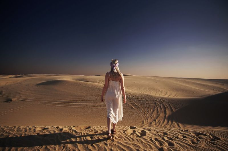 Woman walking on sand dune against sky