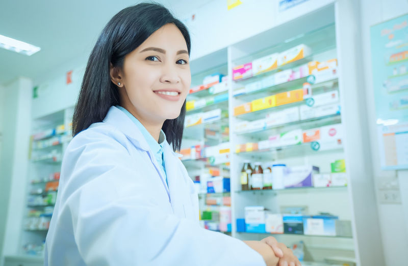 Beautiful smiling young woman pharmacist doing his work in pharmacy. Smiling Occupation Portrait Healthcare And Medicine One Person Adult Indoors  Looking At Camera Women Expertise Lab Coat Clothing Medicine Standing Confidence  Focus On Foreground Hair Young Adult Pharmacy Pharmacist Hairstyle Doctor  Beautiful Woman Responsibility