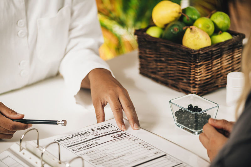Nutritionist explaining nutrition facts label to a client, close-up