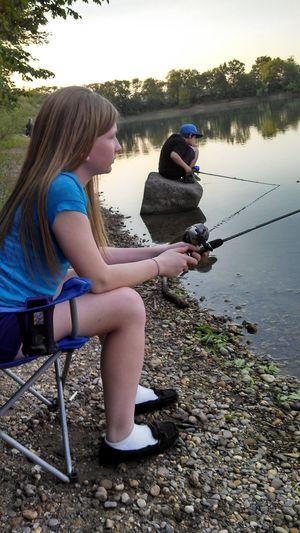Siblings fishing on lakeshore against sky
