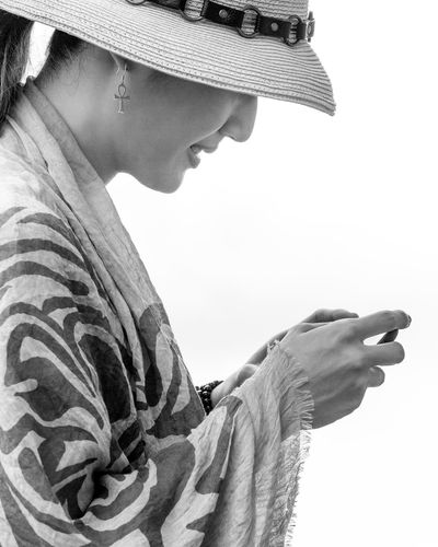 Side view of woman texting against white background
