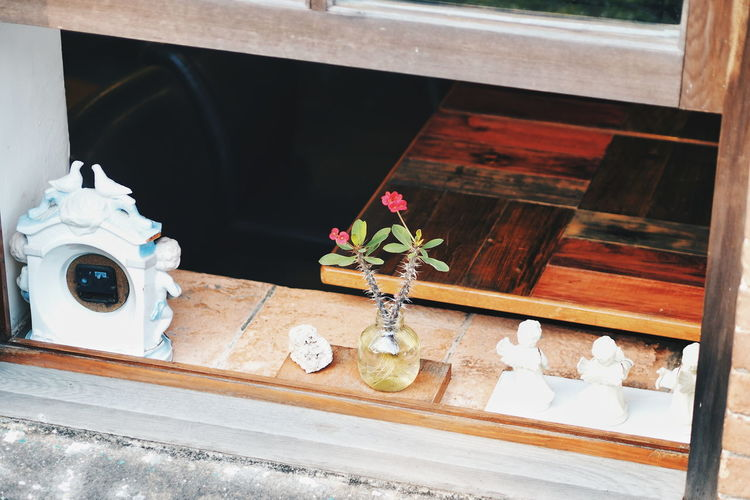 High angle view of flower vase by figurines and alarm clock on window sill