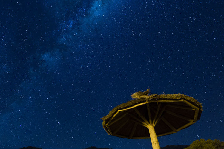 Low angle view of sunshade against star field in blue sky during night
