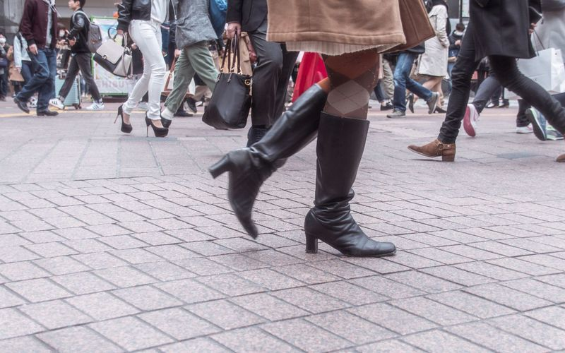Low section of woman wearing high heels boots walking on paved street