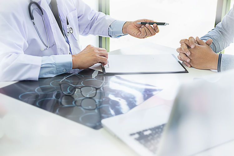 Midsection Of Doctor Giving Pen To Patient At Table