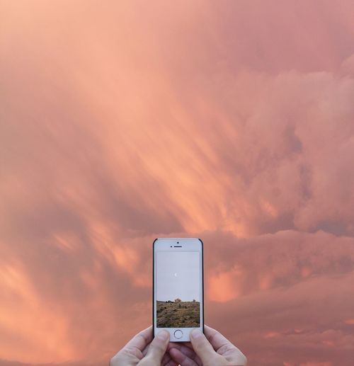 Close-up of hand holding smart phone against sky