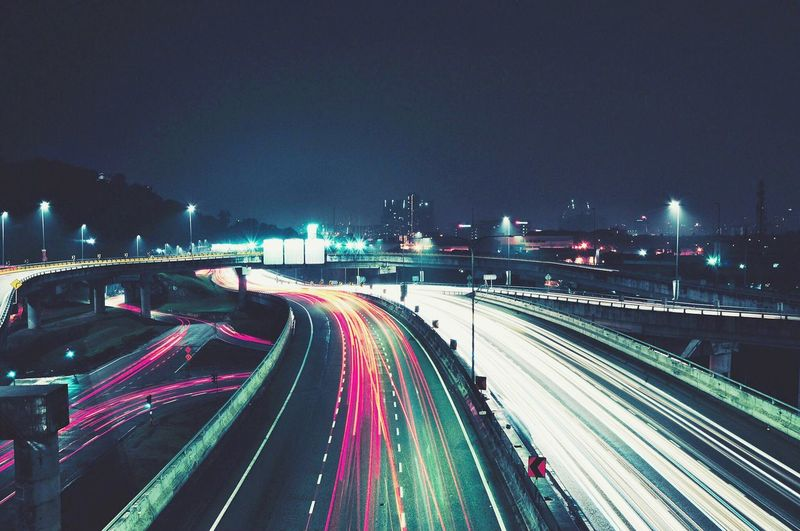 Illuminated light trails on highway in city against sky at night