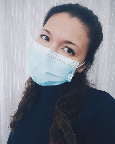 Close-up portrait of young woman wearing surgical mask against wall