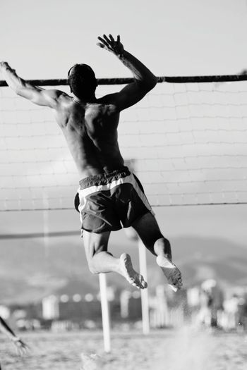 Rear view of man playing beach volleyball