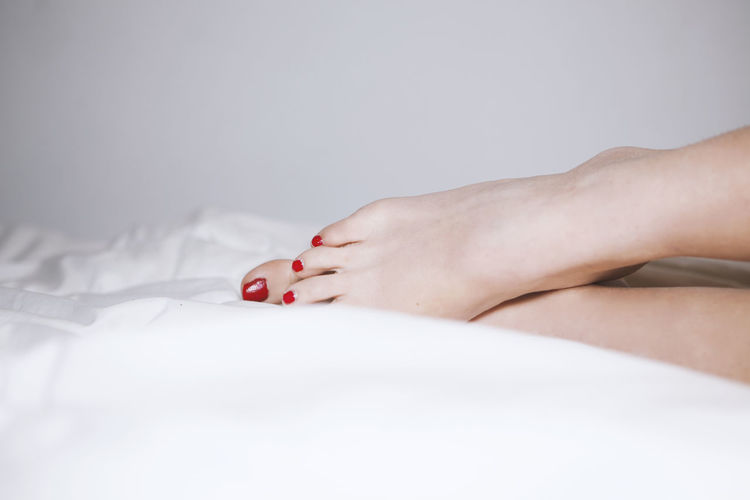 Low Section Of Woman On Bed