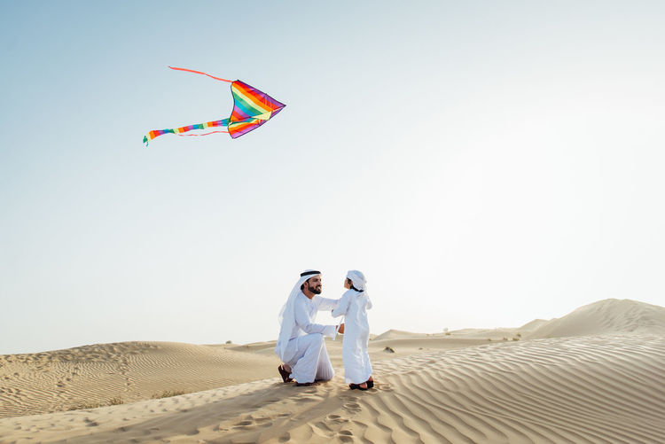 Man and woman standing on sand against clear sky