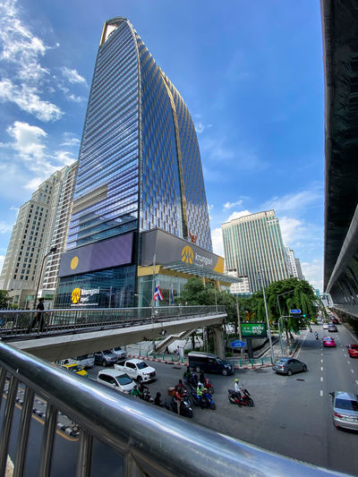 City street by modern buildings against sky