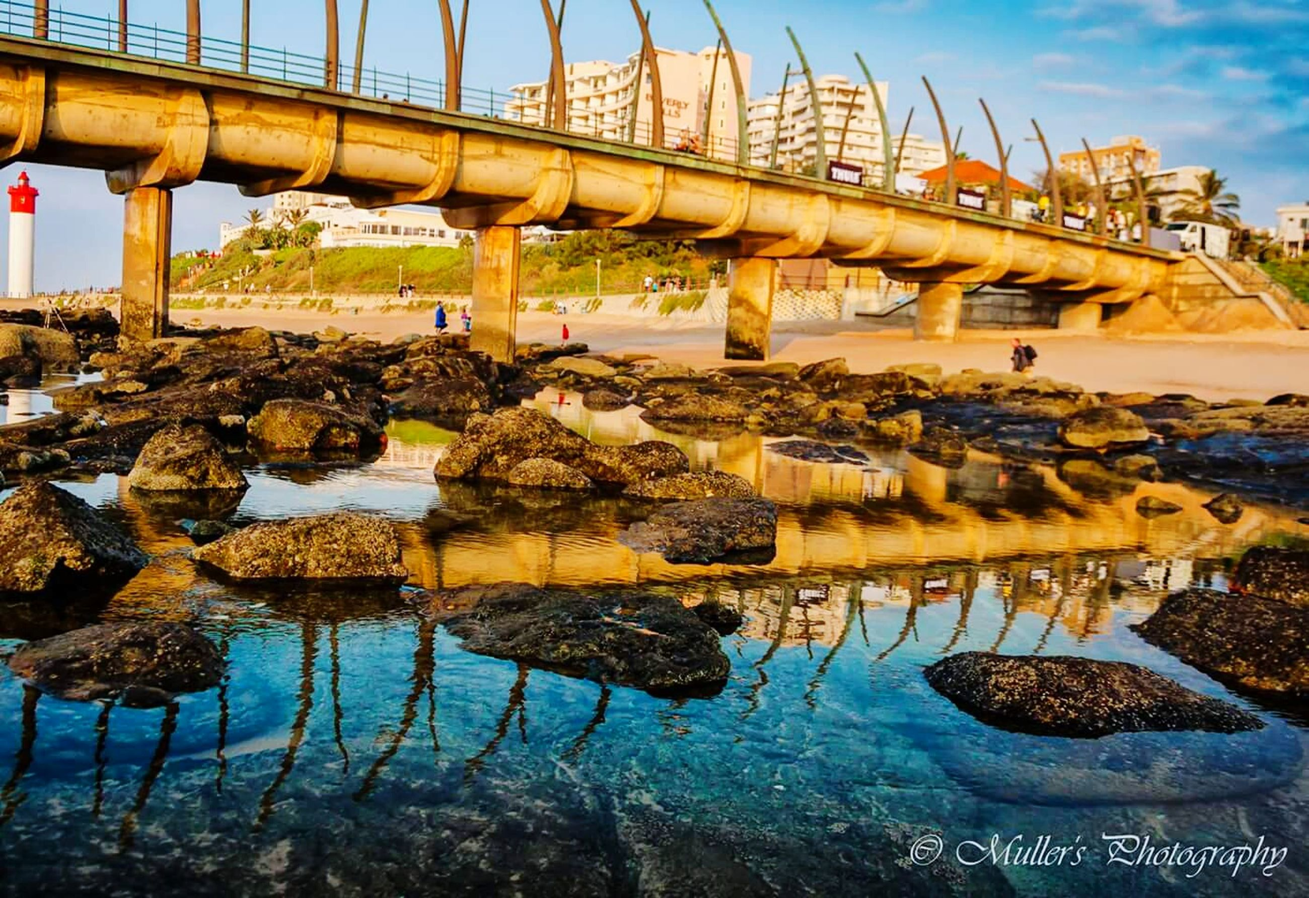 water, sea, built structure, sky, reflection, beach, architecture, nature, river, waterfront, tranquility, rock - object, connection, bridge - man made structure, day, outdoors, scenics, tranquil scene, no people, shore