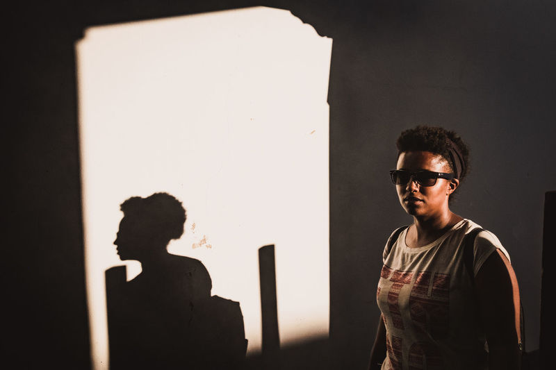 Black Woman Black Girl Portrait Of A Woman Shadows & Lights Silhouette The Street Photographer - 2018 EyeEm Awards African Beauty Backpack Casual Clothing Glasses Golden Hour Lateral View Leisure Activity Lifestyles People Portrait Real People Shadow Standing Stare Street Photography Sunglasses Sunset Waist Up Young Adult