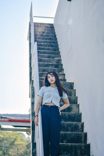 Portrait of young woman standing on staircase by railing at building terrace