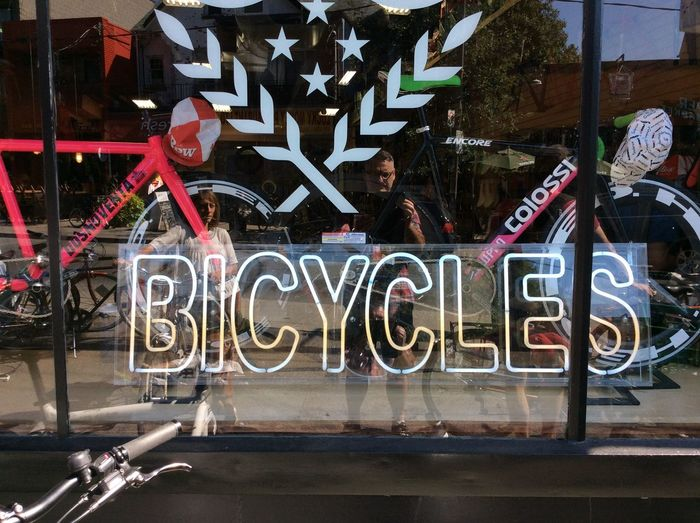 Bikes on Wheels Toronto Canada Shop Front Reflection selfie reflection Neon Sign Handlebars Contemporary Street Life Repair Shop And Sales Woman Cyclist