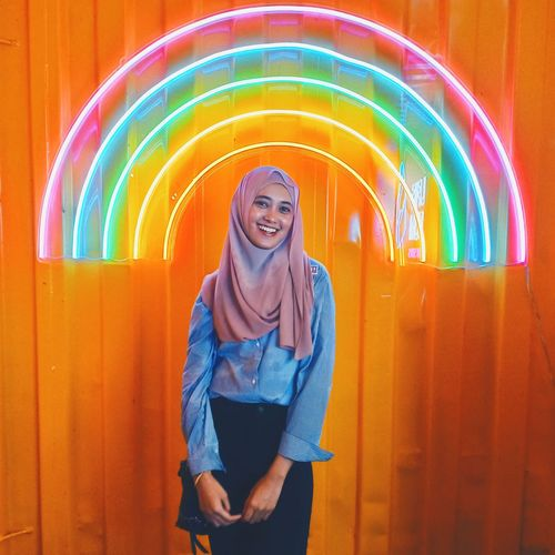 Portrait of smiling young woman standing against multi colored wall