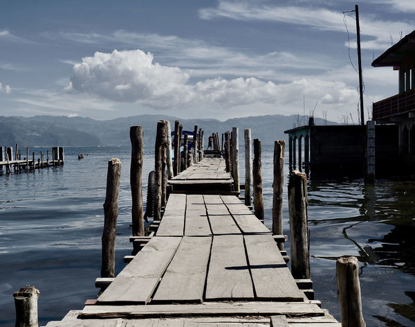 View from a pier in San Pedro on Lake Atitlan, Guatemala. Lonely Low Angle View Perspective Built Structure Cloud - Sky Day Jetty Lake Lake View Muted Colors No People Outdoors Pier Sky Water Wood - Material Wood Paneling