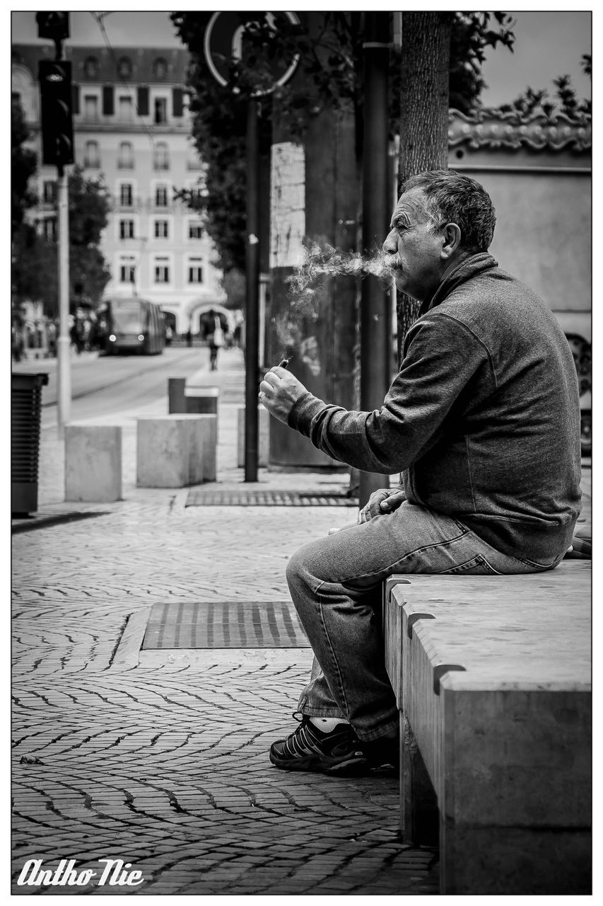sitting, one person, street, outdoors, real people, full length, building exterior, lifestyles, young adult, day, one man only, men, city, adult, adults only, people