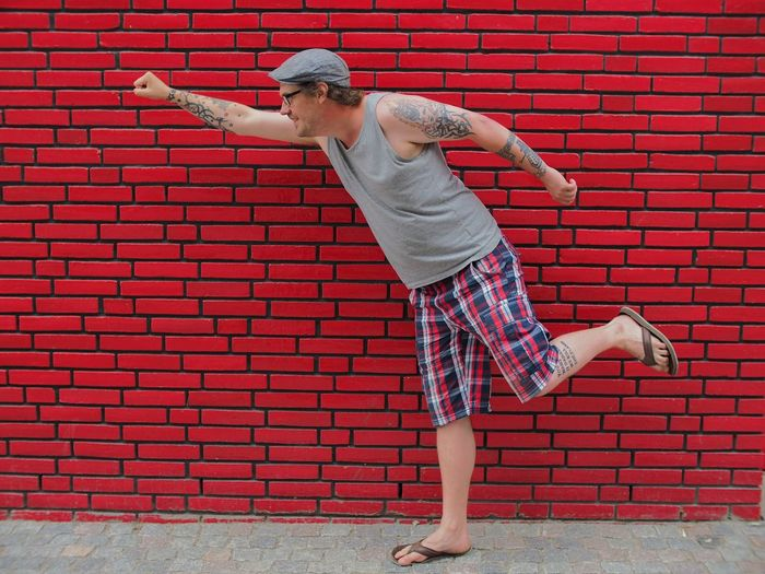 Hipster imitating superhero while standing on sidewalk against red wall
