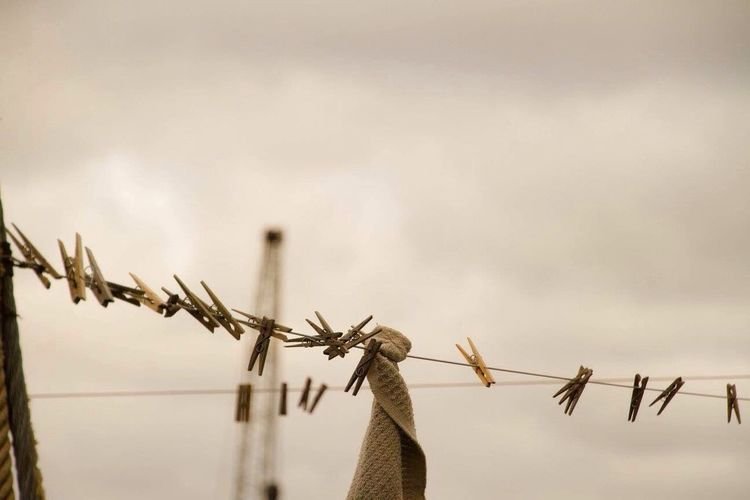 Close-Up Of Pegs On Washing Line Against The Sky