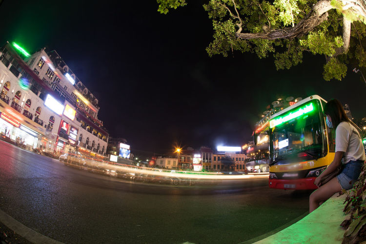 Wide angle shot of city road traffic at night. Illuminated trail of moving transport. Girl sitting at the roadside and the bus is arriving Architecture ASIA Building Centre City City Life City Street Girl Hanoi Horizontal Illuminated Mask Motorbike Night Outdoors Road Roadside Trail Transportation Vietnam