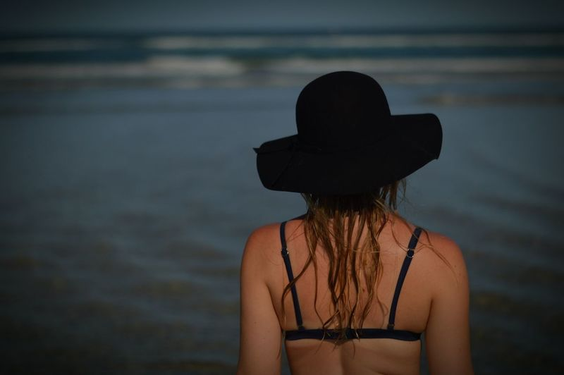Rear view of young woman in sun hat at sea shore