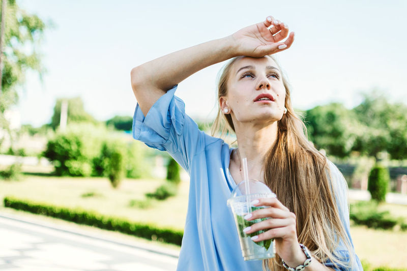 Portrait of a beautiful young woman drinking glass