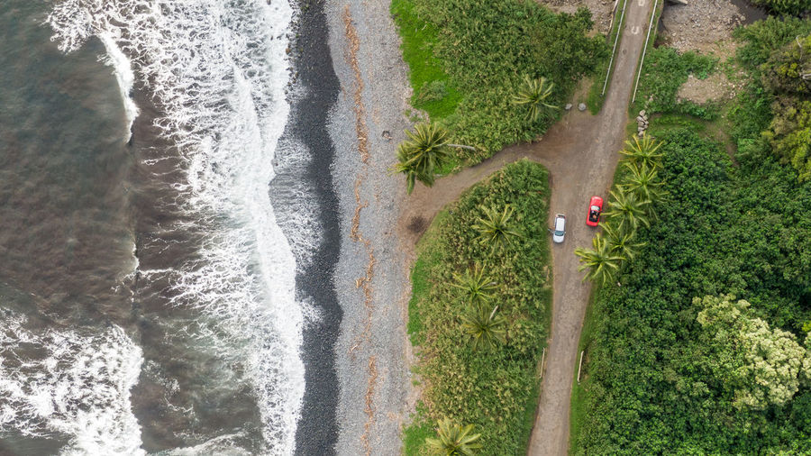 Stunning aerial drone view of a section of the famous Hana Highway south of Hana on the eastern side of the island of Maui, Hawaii. Beautiful black sand beach, waves, rainforest and two cars. Maui Hana Hana Highway Road To Hana Black Sand Beach Black Sand Hawaii Hawaiian Islands Beach Aerial View Drone View East Maui Water Nature Beauty In Nature Scenics - Nature Outdoors Waves Rental Car Car Road Trip Tourism Wild Ocean Dirt Road Rainforest