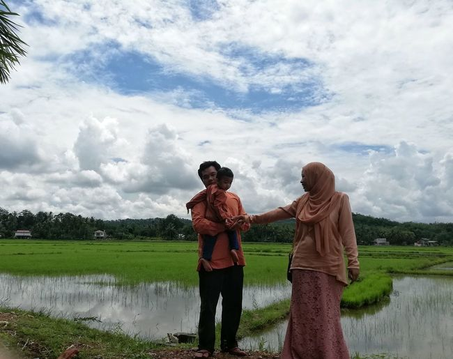 Family standing on field by farm against sky