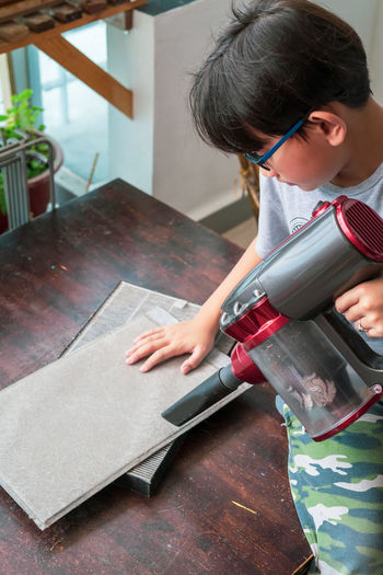 High angle view of boy cleaning on table