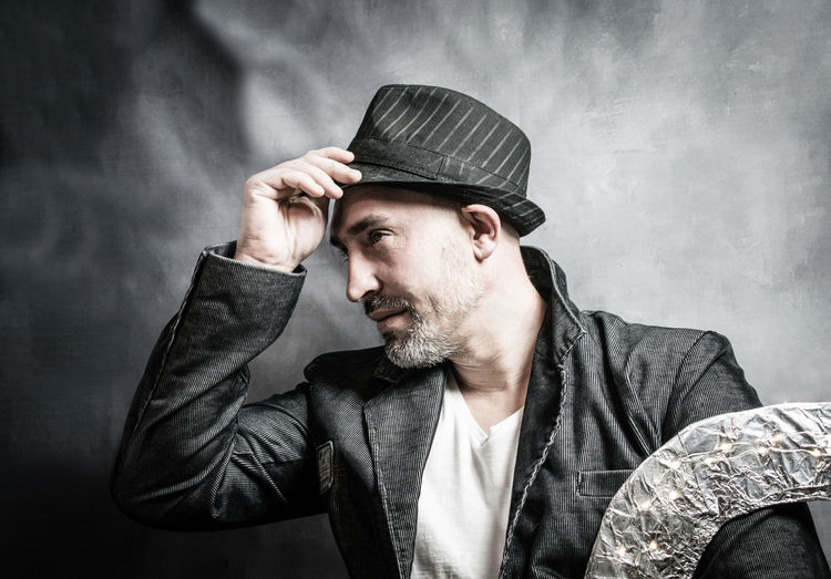 Mature Man Wearing Hat And Blazer Looking Away Against Wall