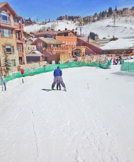 Snow Sports Skiing ❄ View From Behind Child Instructor Snow Ski Instructor Cold Temperature Leisure Activity Winter Sport Togetherness Two People Snowy Mountains Snow Sport Ski Resort  Ski Slope Snow Skiing Architecture Winter Sky Winter Scene Snow Resort Motion Showing Action Movement
