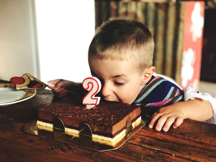 Boy Eating Birthday Cake At Table