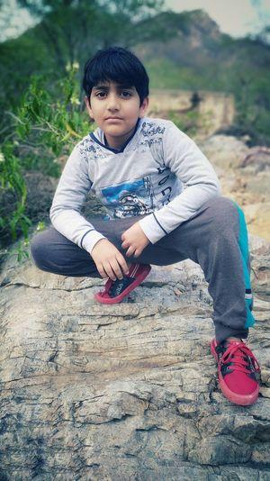 Portrait of boy crouching on rock