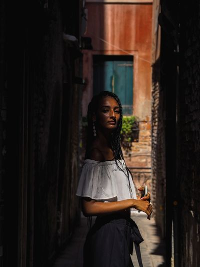 Side view of young woman standing in alley