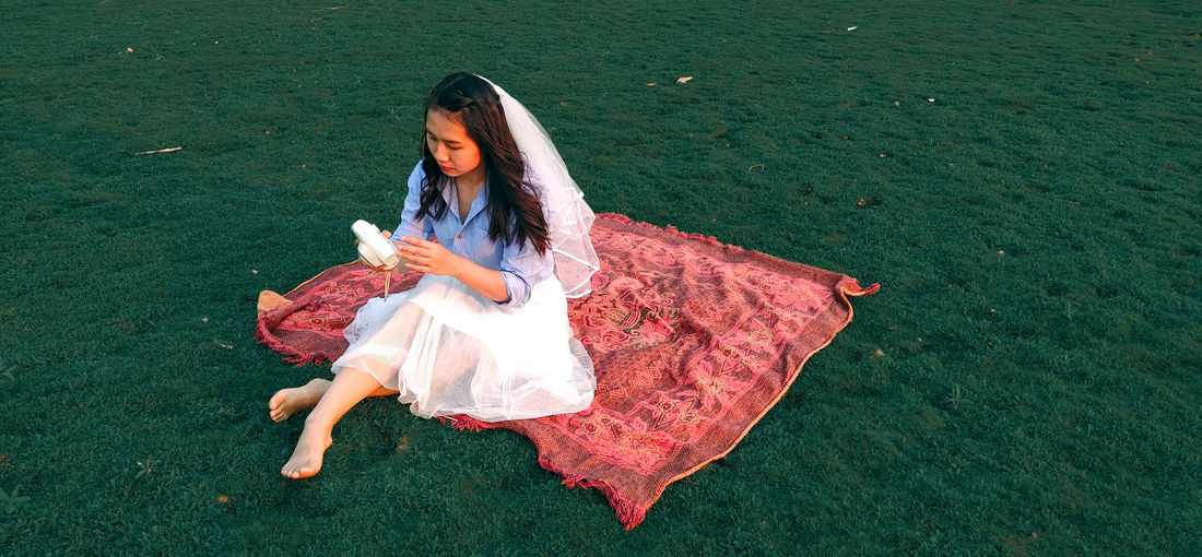 High angle view of woman sitting on blanket amidst grass