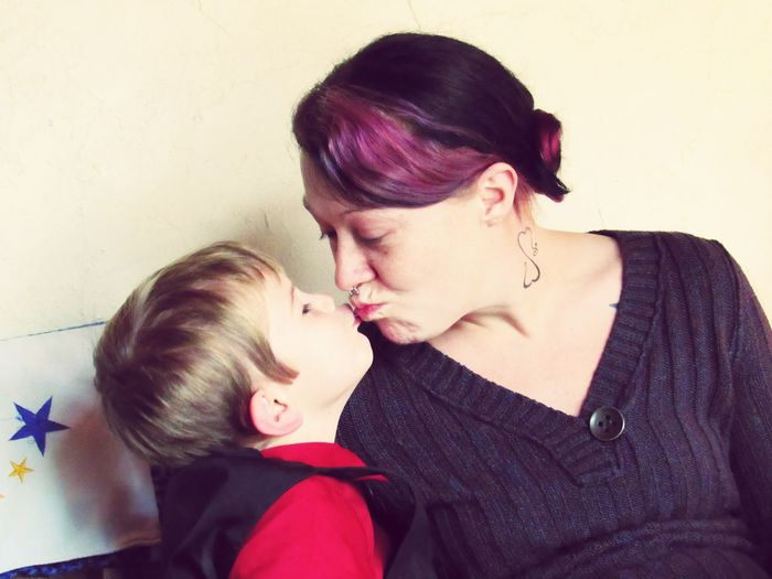Mother and son kissing at home