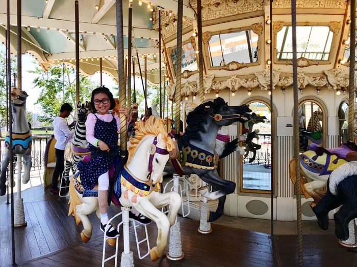 Carousel Carousel Real People Childhood Child Lifestyles Amusement Park Arts Culture And Entertainment Sitting Outdoors