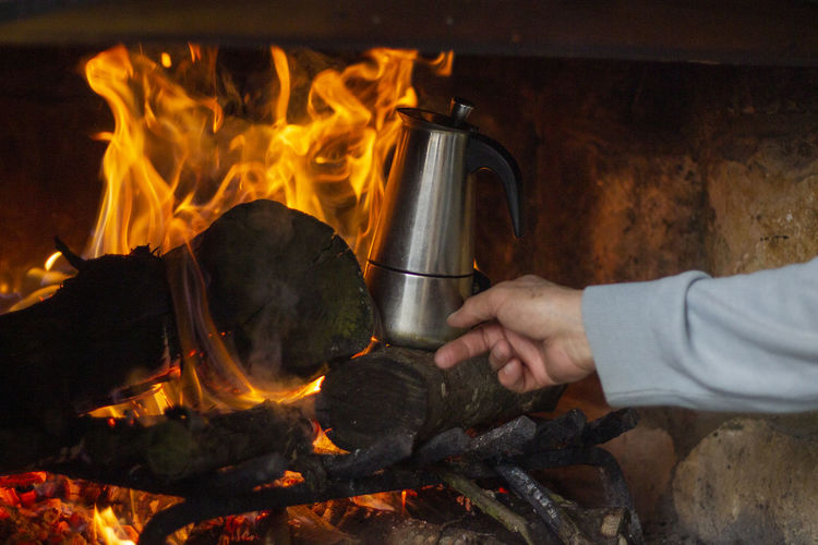Close-up of hand holding kettle in fireplace