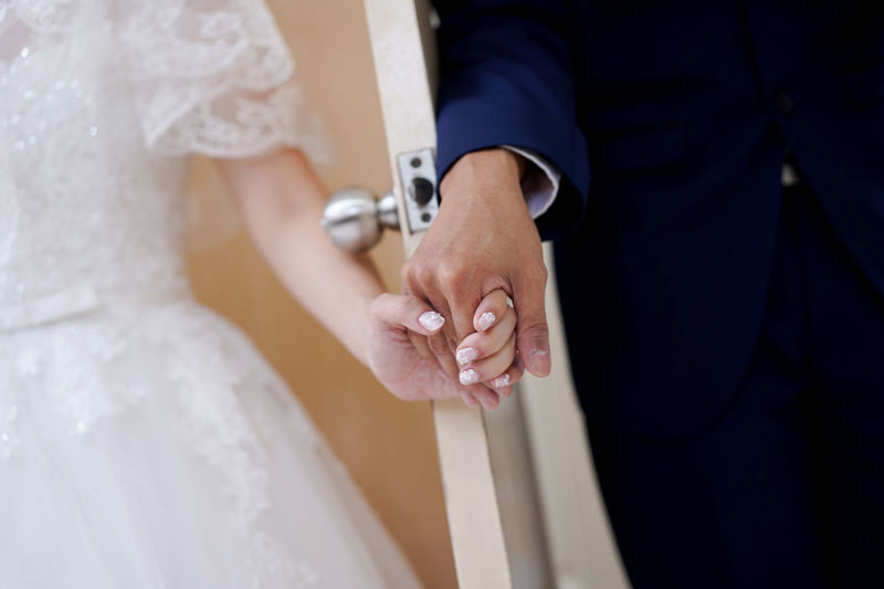 Young wedding couple holding hands in between the door Wedding Dress Life Events Wedding Newlywed Bride Midsection Celebration Adult Event Married Two People Women Hand Love Men Bridegroom Human Hand Couple - Relationship Emotion Positive Emotion Wedding Ceremony Wife Holding Hands