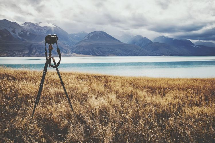 Camera on tripod over land by lake against sky