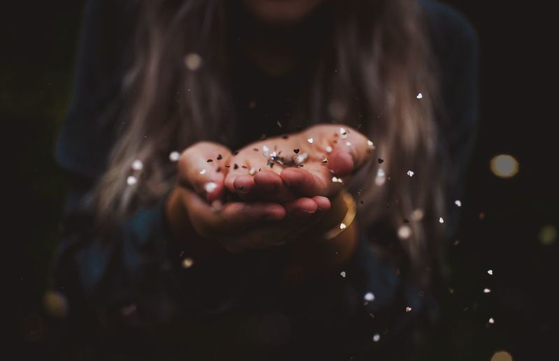 Close-Up Of Young Woman Blowing Glitter Off Of Palms