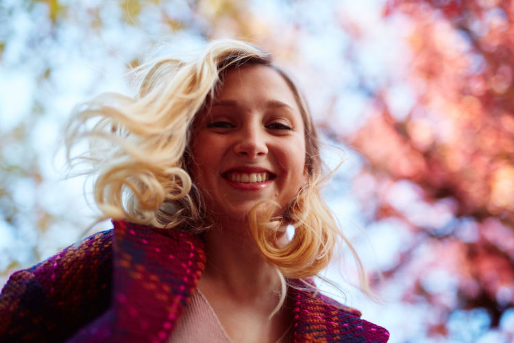Autumn Beautiful Woman Blond Hair Cheerful Close-up Day Focus On Foreground Happiness Headshot Leisure Activity Lifestyles Long Hair Nature One Person One Woman Only One Young Woman Only Outdoors Portrait Real People Sky Smiling Tree Warm Clothing Young Adult Young Women