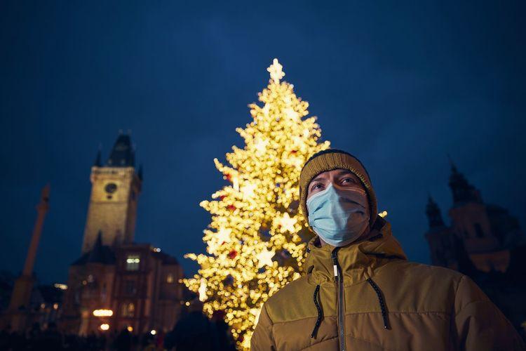 Low angle of man against illuminated christmas tree at night