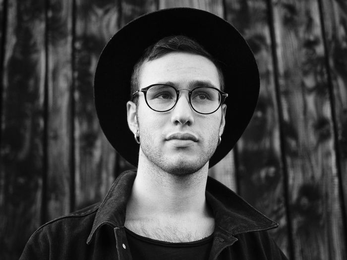 Young Man Wearing Eyeglasses And Hat Against Wooden Wall