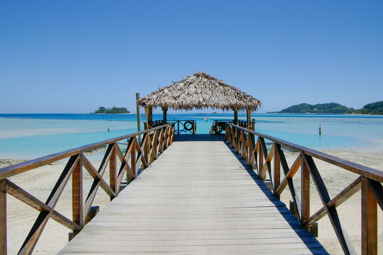 Sea Water Sky Clear Sky Tranquility Beauty In Nature Nature Scenics - Nature Thatched Roof Tranquil Scene The Way Forward Direction Railing Architecture Built Structure Pier Wood - Material Horizon Over Water Blue No People Outdoors Wood Wood Paneling Fiji Islands