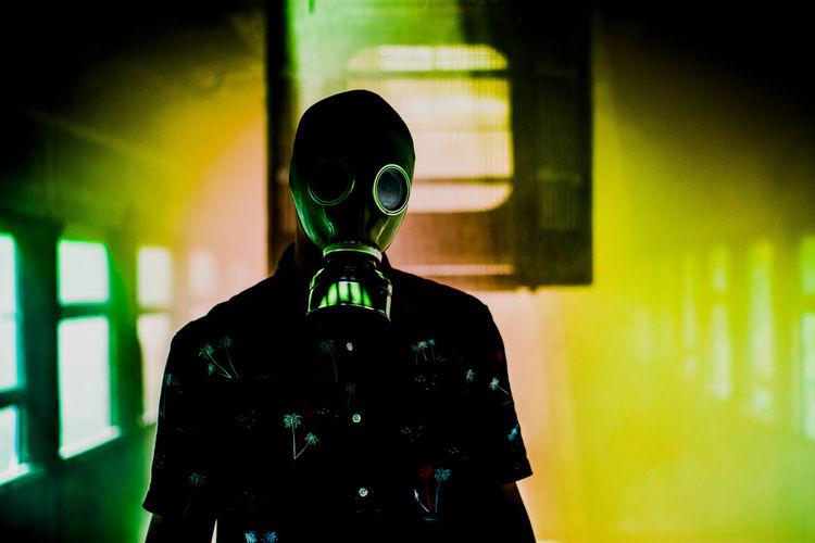 Teenage boy wearing gas mask while standing amidst smoke