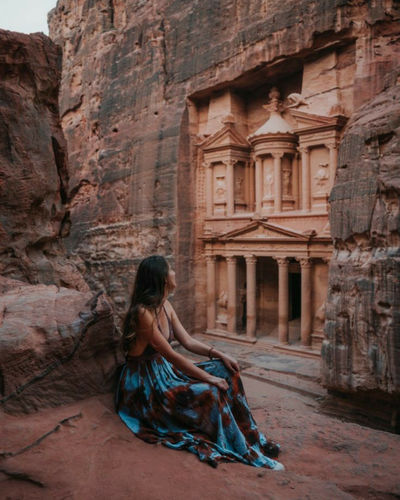 Full length of woman sitting against ancient structure