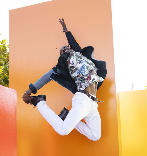 Low angle view of man jumping against wall